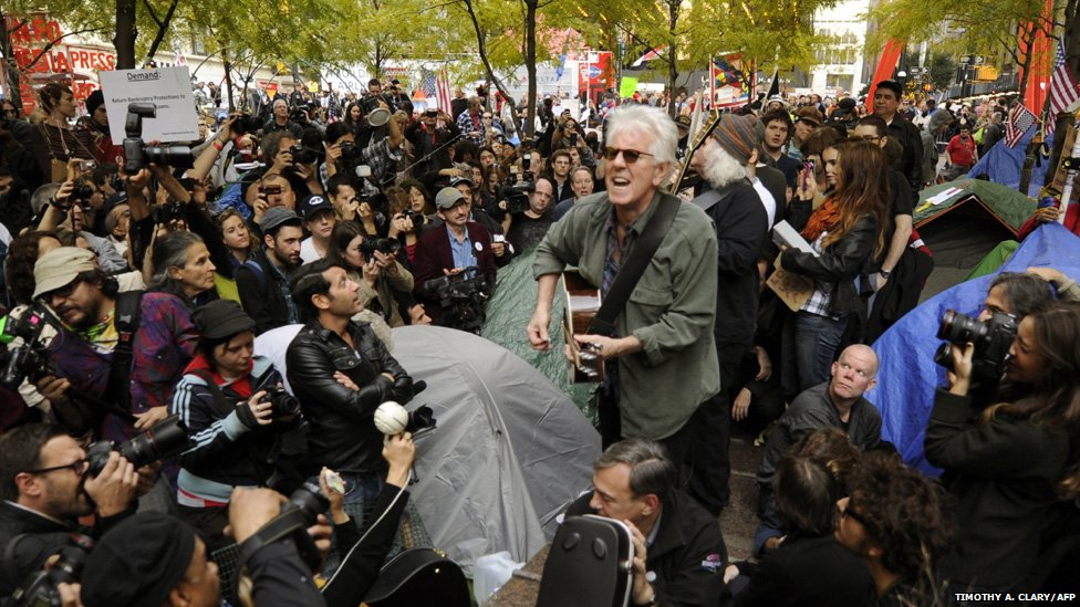 Musicians Graham Nash and David Crosby (behind) perform for demonstrators