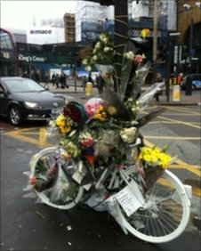 A ghost bike tribute and flowers where a cyclist died near King's Cross
