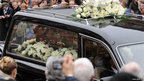 Sir Jimmy Savile's coffin in hearse drives by crowds in Leeds