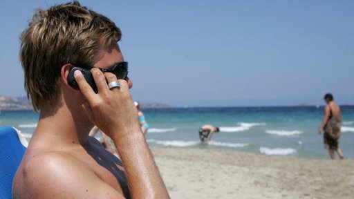 An English tourist uses his mobile phone on Playa D'En Bossa beach
