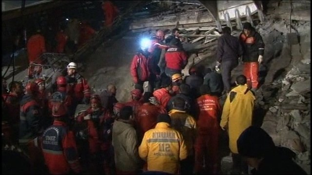 Rescue workers on rubble