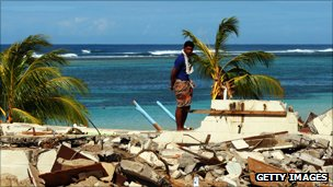 Man looks at damage caused by tsunami