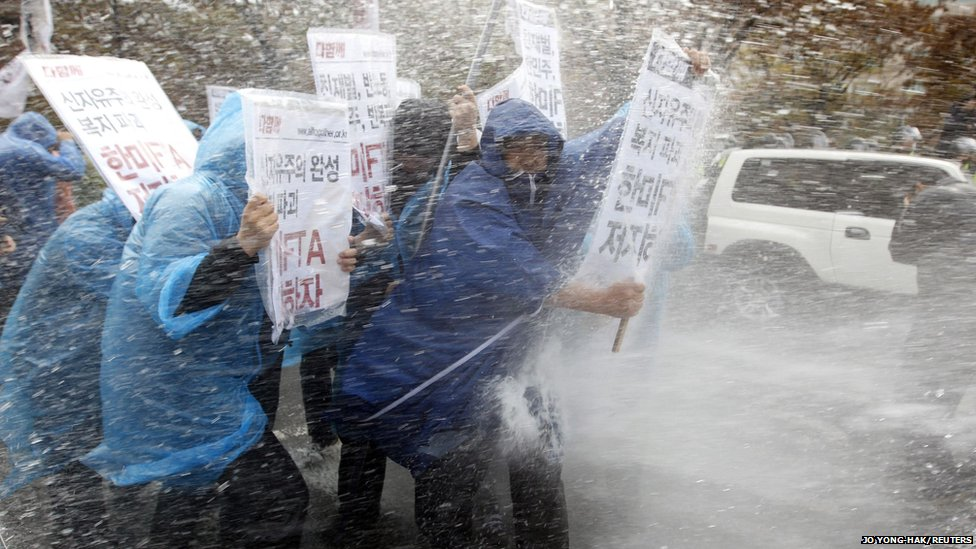 Protesters holding placards (stating Block the South Korea-US FTA! ) are hit by water cannon