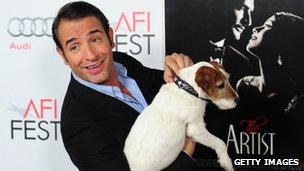 Actor Jean Dujardin poses with Uggie the dog on arrival for the Gala screening of The Artist