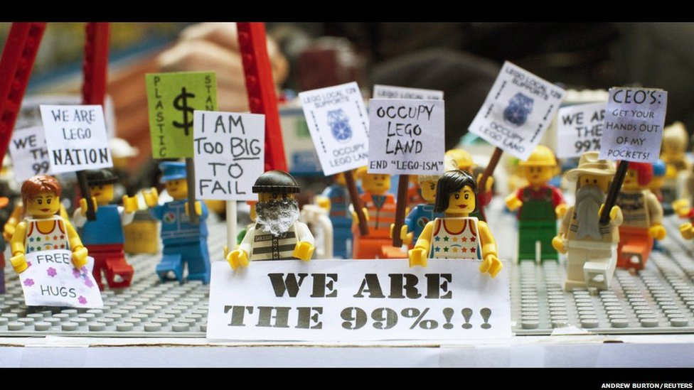 Toy Lego characters, holding signs in support of the Occupy Wall Street movement, are seen on a table in Zuccotti Park, New York