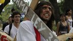 Student protester dressed as Christ carrying his cross