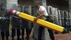 Student using giant pencil eraser to clean paint off police riot shield
