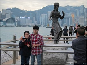 Tourists pose for pictures in front of the statue of martial arts movie star Bruce Lee
