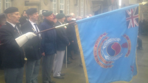 A flag is lowered during a service in Queen's Square in the centre of Wrexham