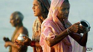 Hindu pilgrims offer prayers while taking a ritual bath in the Ganges