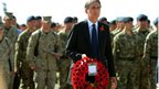 Philip Hammond carries a wreath of poppies