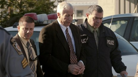 Jerry Sandusky (C) is led away by police in Harrisburg, Pennsylvania, on 5 November 2011