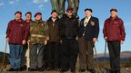 Seven elderly veterans stand in front of a war memorial