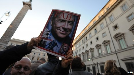 Demonstrator holds copy of Time magazine outside Mr Berlusconi's offices in Rome - 12 November
