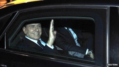Prime Minister Silvio Berlusconi waves as he leaves his residence in Rome, 12 November 2011