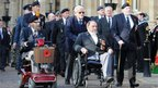 War veterans in a Remembrance Day parade pass by Northampton's Guildhall.