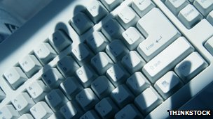 A hand's shadow over a computer keyboard