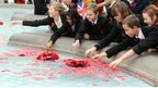 children leaning into fountain to throw poppies in