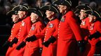 Group of Chelsea Pensioners march from right to left.