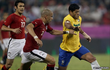 Ahmed Hassan (17) of Egypt. Givanildo Vieira (R) of Brazil vies for the ball with Wael Goma of Egypt (L)
