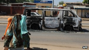 Young girls walk past a burnt vehicle in Nigeria's Damaturu town in Yobe state on 7 November
