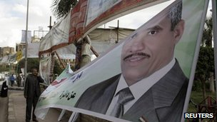 An election worker hangs a candidate&#039;s poster in Cairo - 14 November 2011