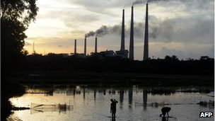 Indian labourers prepare a flooded field for rice farming in front of chimneys of Kolaghat Thermal Power Plant in Mecheda