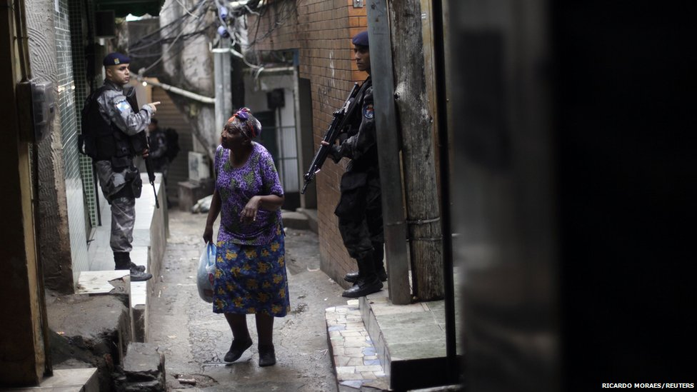 An elderly woman walks past policemen patrolling the Rocinha slum