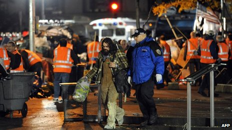 A man is escorted by a New York Police Department officer as New York City sanitation workers clear Zuccotti Park