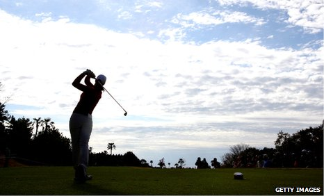 A female golfer tees off