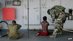 A soldier guards two suspected Somali pirates aboard a French warship (generic image)