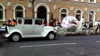 The wedding cars line up behind the carriage