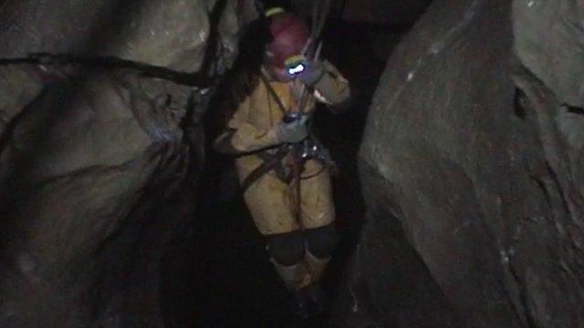 Caver hanging between rocks