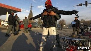An Afghan policeman searches a man at a checkpoint on the first day of the loya jirga