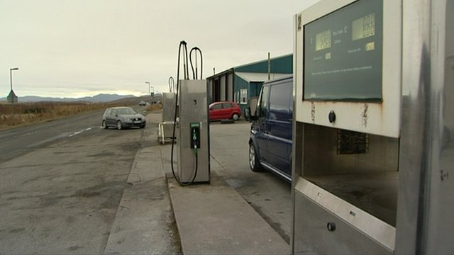 Cars at fuel pumps on a remote road