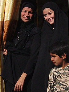 Um Ahmed (L) at home with her daughter and son