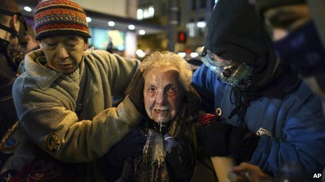 Dorli Rainey, 84, is helped away after police pepper-sprayed demonstrators at Occupy Seattle, 15 November