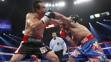 Juan Manuel Marquez (left) with the PRI logo on his left leg and Manny Pacquiao (right) during their fight
