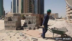 A construction worker pushing a wheelbarrow in the financial district of Doha, Qatar (file photo)
