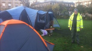 Protestor in hi-vis jacket and tents