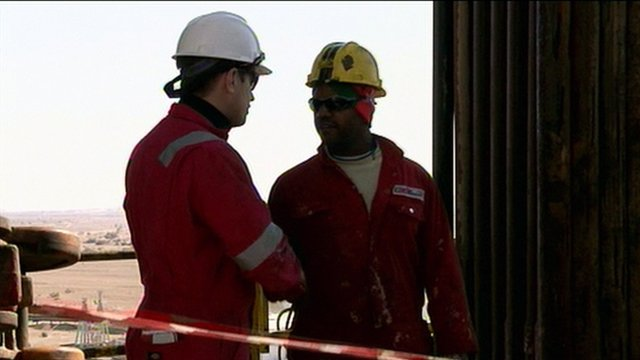 Oil workers shake hands