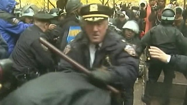 New York police officer, carrying baton, struggles with protester