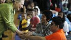 US Secretary of State Hillary Clinton greets a blind flood victim in Bangkok