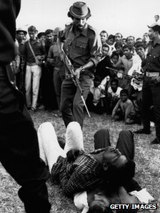 A Mukti Bahini guerrilla about to bayonet  men accused of collaboration with Pakistan during Bangladesh's war of  independence, at a racecourse in Dhaka, 1971
