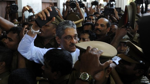 Sarath Fonseka is escorted by police as he arrives at the Colombo High Court in Colombo