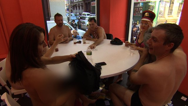 A table of naked men and women play cards inside of a display case.