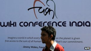 A participant walks past a poster advertising Wikipedia's Mumbai meeting