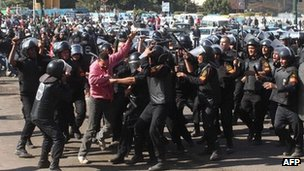 Egyptian riot policemen scuffle with a protester at Cairo's landmark Tahrir Square on Saturday following clashes after police dispersed a sit-in