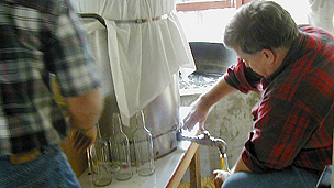 A man pouring cane syrup