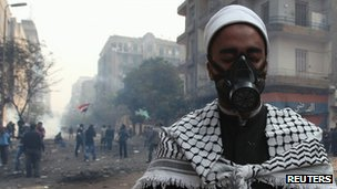 Egyptian cleric, and protester, prays as fellow protesters run from tear gas during clashes near the interior ministry in Cairo on 22 November 2011